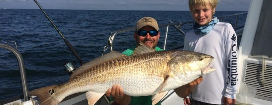 young boy with large red drum